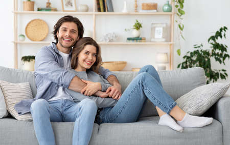 Photo pour Beautiful couple hugging while sitting on couch at home, spending weekend together, copy space. Young man and woman in love resting at living room, posing at camera, family, love, marriage concept - image libre de droit