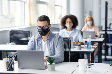 Photo pour Teamwork in corporate company and returning to work after quarantine covid-19. Focused millennial man in glasses and protective mask works at laptop at workplace with antiseptic in office interior - image libre de droit