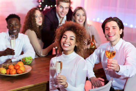 Photo pour Cheers, Merry Christmas. Friends Holding Glasses Toasting Celebrating Xmas Sitting At Table Indoors, Smiling To Camera. - image libre de droit