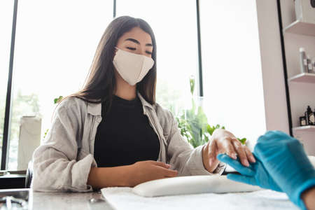 Opening of beauty studio after lockdown. Asian woman client in protective mask looks at master in rubber gloves, doing manicure and files nails in salon on window background, cropped, free space