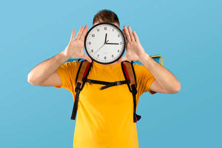 Photo pour Time to travel concept. Young man with camping equipment holding clock in front of his face over blue studio background. Millennial guy ready to start his hiking journey or vacation - image libre de droit