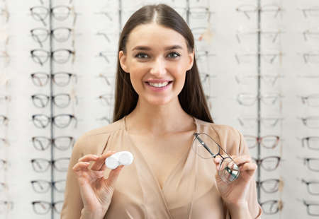 Photo pour Ophthalmology Concept. Portrait of smiling young woman with myopia showing to camera eyeglasses and contact lenses standing in the optical shop, holding plastic case and specs in both hands - image libre de droit