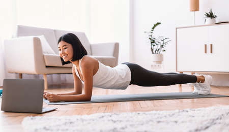 Photo for Training At Home. Full length portrait of sporty smiling asian woman doing plank while watching online tutorial on laptop computer, exercising in living room on the floor on yoga mat, free space - Royalty Free Image