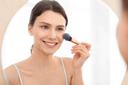 Photo pour Closeup of attractive young woman applying blush on her face, sitting in front of mirror, copy space. Smiling attractive young lady doing makeup before going out, shot over shoulder in bedroom - image libre de droit