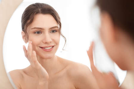 Photo pour Closeup of cheerful young lady using face cream at home, looking at mirror and smiling. Attractive woman applying beauty product on her cheeks, nourishing her sensitive skin in winter, face care - image libre de droit