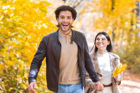 Photo pour Emotional guy running buy golden autumn forest with his girlfriend, copy space - image libre de droit