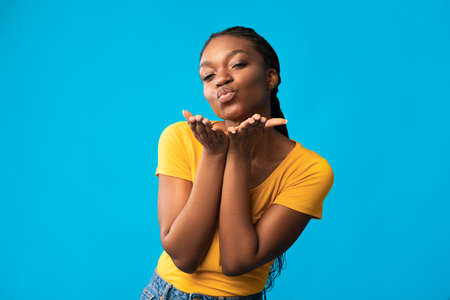 Photo pour Pretty Black Young Lady Blowing Air Kiss Sending Kisses Flirting Posing Over Blue Background, Standing In Studio And Smiling To Camera. Love And Romance, Female Playful Gesture Concept - image libre de droit