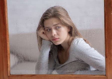 Photo pour Sad young woman sitting at home and looking out window at falling rain. Lonely lady suffering from autumn depression, feeling alone, hopeless or melancholic. Mental health concept - image libre de droit