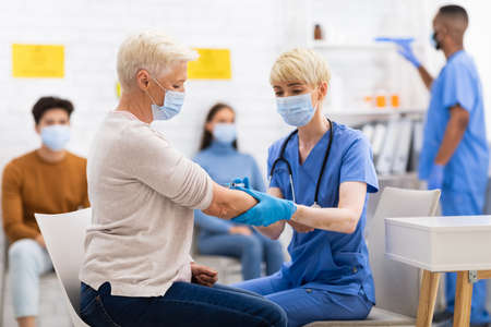 Photo pour Senior Patient Lady Getting Vaccinated Against Corona virus Sitting With Doctor In Hospital, Wearing Face Mask. Nurse Injecting Corona Virus Vaccine Shot To Older Woman - image libre de droit