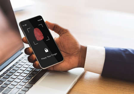 Photo pour Biometric Identification Concept. African American Man Holding Cellphone In Hand, Showing Application For Fingerprint Scanning With A Zone To Touch With Thumbprint Icon On The Device Screen - image libre de droit