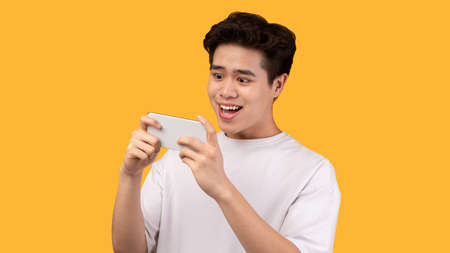 Foto de Portrait of excited overjoyed asian guy playing video games on smartphone isolated over yellow studio background, copy space. Satisfied male adult using his gadget - Imagen libre de derechos