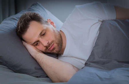 Photo for Depressed Man Having Insomnia Unable To Sleep Lying In Bed In Bedroom At Home At Night. Sleeplessness, Mental Health Problem, Male Depression Concept. Low Light - Royalty Free Image