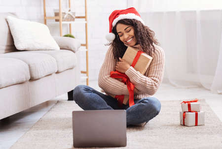 Photo for Christmas And New Year Presents. Happy Black Lady Holding And Embracing Gift Box, Sitting On The Floor At Home In Living Room With Laptop Computer, Celebrating Online, Making Video Conference - Royalty Free Image