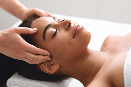 Photo pour Unrecognizable masseuse massaging relaxed black lady head, closeup African american young woman wrapped in towel having relaxing therapy at newest luxury spa salon, spending her weekend at spa - image libre de droit