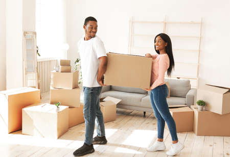 Photo for African American tenants carrying cardboard box with belongings in new home. Young black homeowners moving into their purchased property together, unpacking possessions - Royalty Free Image