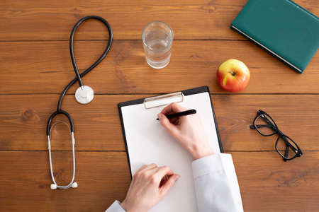 Photo pour Recommendations and prescription from doctor. Woman in white coat writes on tablet at workplace, on wooden table with stethoscope, glasses, apple and glass of water, top view, copy space, cropped - image libre de droit