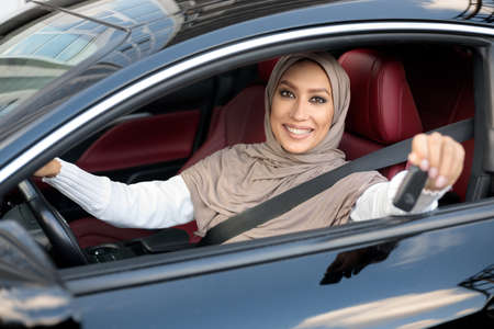 Photo pour Car Buyer. Young Muslim Female Client In Hijab Smiling And Showing Automobile Keys Sitting In Her New Vehicle. Confident And Beautiful Middle East Woman Choosing Auto In Dealership Showroom Store - image libre de droit