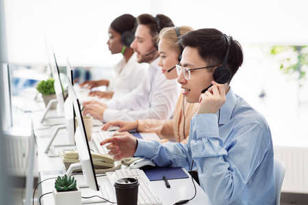 Photo for Telecommunications concept. Positive hotline consultants selling goods or services at call centre, copy space. Diverse team of tech support managers dealing with customers needs at modern office - Royalty Free Image