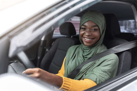 Photo pour Portrait of joyful african muslim woman in car, enjoying road trip, smiling black islamic lady in hijab driving her new vehicle, holsing steering wheel and smiling at camera, closeup shot - image libre de droit