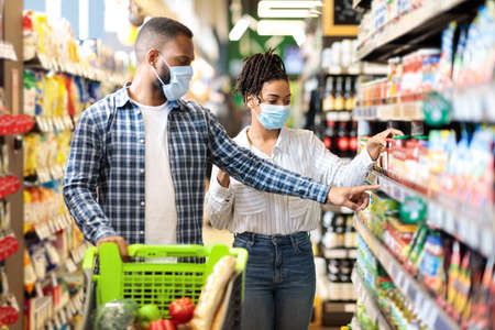 Photo pour African Husband And Wife In Protective Face Masks Shopping Groceries In Supermarket Buying Food Essentials Walking With Shop Trolley Cart In Grocery Store Indoor. Family Preparing For Quarantine - image libre de droit