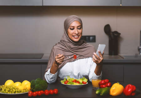 Photo pour Happy Muslim Woman Using Smartphone Eating Vegetable Salad Having Lunch Sitting In Kitchen At Home. Dieting Mobile Application, Healthy Nutrition And Food, Weight Loss Recipes App For Phone - image libre de droit