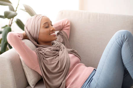 Photo pour Lovely black lady in hijab lying on sofa, closing her eyes and smiling, taking nap at midday, indoors. Attractive Muslim woman in traditional headscarf relaxing on comfy couch at home - image libre de droit