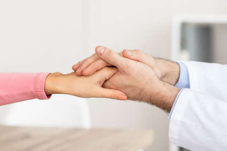 Photo for Empathy And Encouragement Concept. Close up of male doctor comforting female patient, holding hands during appointment at his office in hospital. General practitioner cheering young sick lady - Royalty Free Image