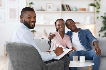 Photo pour Family Psychotherapy. Happy Black Spouses And Marital Counselor Posing At Office After Successful Marital Therapy, Loving Couple Embracing On Couch And Therapist Smiling At Camera, Selective Focus - image libre de droit