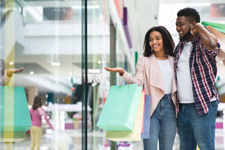Foto für Discount Prices. Smiling Black Couple Shopping In Mall Together, Looking At Showcase With Interest, African Spouses Walking In Department Store With Bright Shopper Bags, Enjoying Seasonal Sales - Lizenzfreies Bild