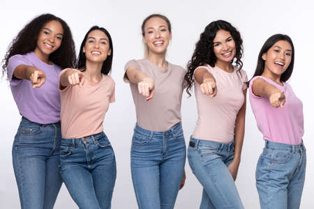 Photo pour Youre Next. Positive Diverse Females Group Pointing Finger At Camera Smiling Posing Over White Studio Background. We Choose You Concept. Advertisement Banner - image libre de droit