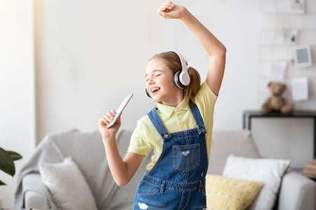 Foto de Having Fun. Portrait of overjoyed teen girl singing song and using smart phone as microphone, wearing wireless headset. Carefree schoolgirl dancing at home in living room, copy space - Imagen libre de derechos