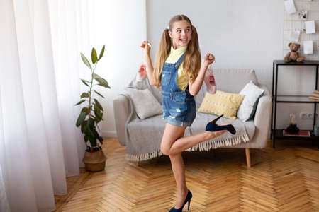 Foto de Having Fun. Full length shot of excited female teenager with two ponytails wearing and posing in blue high heels shoes, holding pink sneakers by laces, standing in living room, looking away - Imagen libre de derechos