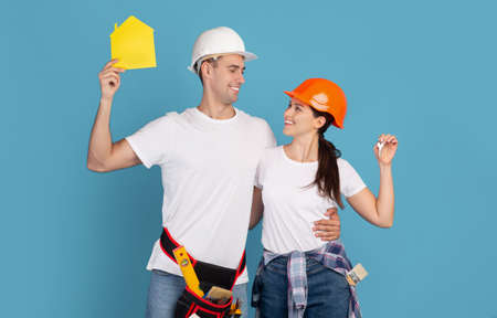 Photo pour Home Improvement. Happy Young Couple In Hardhats Holding Yellow Paper House Figure And Keys, Enjoying Making Renovation Together, Celebrating Buying Property, Standing Over Blue Background, Copy Space - image libre de droit