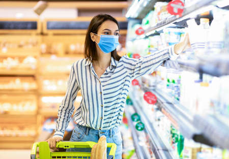 Photo pour Consumerism And Consumption. Female customer in disposable face mask choosing dairy products, holding bottle of milk or yoghurt. Woman standing with shopping trolley near the fridge in mall - image libre de droit