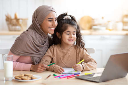 Photo pour Smiling Muslim Mother And Her Little Daughter Using Laptop In Kitchen Together, Loving Islamic Mom Helping Girl With Online Education And Development Activities, Looking At Computer Screen And Smiling - image libre de droit