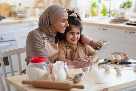 Photo pour Smiling Muslim Mom And Her Little Daughter Using Digital Table In Kitchen, Checking Dough Recipe Online While Preparing Pastry Together, Happy Islamic Mother And Cute Girl Cooking At Home, Free Space - image libre de droit