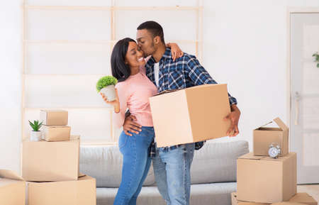 Affectionate black guy kissing and hugging his wife, holding carton box and house plant on moving day, panorama. Loving man and his girlfriend unpacking belongings in their new apartment