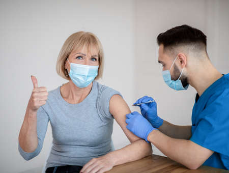 Photo for Mature woman in face mask approving of covid-19 vaccination, showing thumb up gesture during coronavirus vaccine injection at clinic. Male doctor immunizing senior patient against viral disease - Royalty Free Image