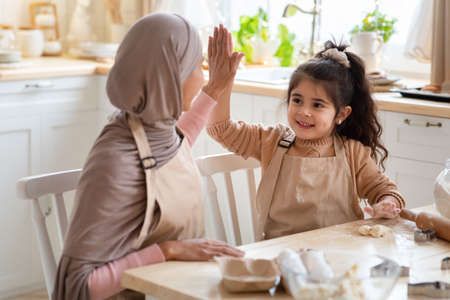 Photo pour Cheerful Muslim Mom And Daughter Giving High Five To Each Other While Baking In Kitchen. Happy Islamic Family Preparing Homemade Food, Having Fun And Enjoying Spending Time Together At Home, Closeup - image libre de droit