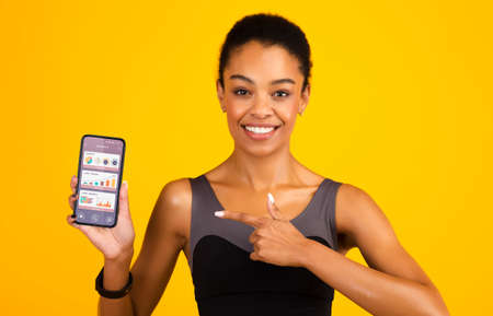 Photo for Sporty African Woman Showing Mobile Phone With Jogging App Recommending Running Application For Sport Trainings Over Yellow Studio Background, Smiling To Camera - Royalty Free Image