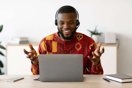 Photo for Online Tutoring. Male African Teacher In Headset Having Web Lesson With Laptop, Smiling Black Coach Wearing Traditional Ethnic Shirt, Gesturing And Talking At Camera, Enjoying Distance Training - Royalty Free Image