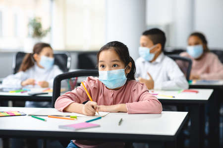 Photo pour Education During Pandemic. Asian girl sitting at table in classroom at school or kindergarten, wearing surgical face mask, writing or drawing in notebook. New Normal, Safe Learning - image libre de droit