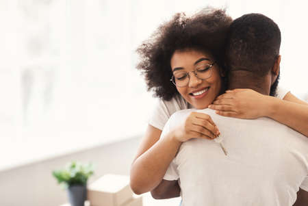 Photo pour Family Housing Concept. Happy African Couple Holding New House Key Embracing Celebrating Moving Apartment Standing Indoors. Real Estate Owners. Copy Space - image libre de droit