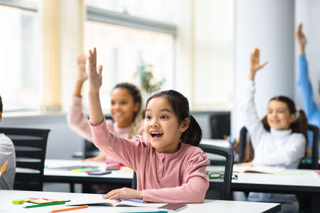 Photo pour Education, Elementary School, Learning and People Concept. Diverse group of smart junior school kids sitting at desks in classroom and raising hands for an answer, studying with pleasure - image libre de droit