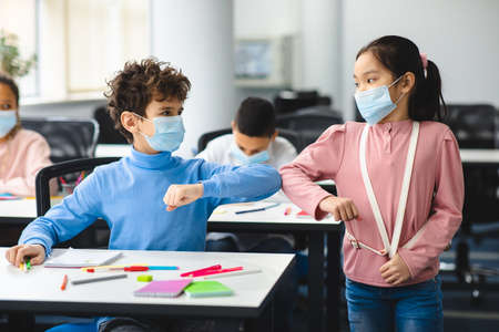 Photo for Stop Spreading Virus Concept. Small diverse schoolchildren wearing protective face masks greeting each other and bumping elbows at classroom. Boy sitting at desk, girl standing with backpack - Royalty Free Image