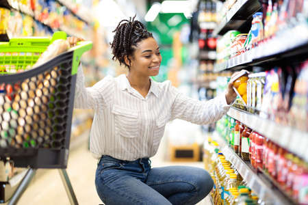 Photo pour African Woman Buyer Choosing Products Doing Grocery Shopping Buying Healthy Organic Food In Local Supermarket, Posing With Shop Cart Full Of Groceries. Happy Female Customer Concept - image libre de droit