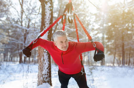Outdoor bungee fitness. Athletic senior man working out with suspension training straps at snowy winter forest. Strong mature sportsman exercising his arms using sports equipment outside