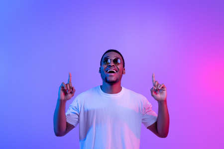 Photo pour Excited Black Guy Standing Under Neon Light Pointing Fingers Up At Copy Space , Cheerful African American Man In Stylish Sunglasses Demonstrating Free Space Above His Head Over Purple Background - image libre de droit