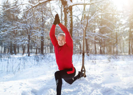 Outdoor winter fitness concept. Sporty senior man training with resistance straps at snowy forest. Fit mature guy exercising with sports equipment outside in cold frosty weather