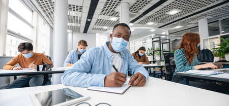 Photo pour Education Concept. Portrait of black guy wearing disposable surgical mask sitting at desk in classroom at highschool, writing test in notebook, taking notes during lecture, looking at camera, panorama - image libre de droit